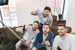 Delighted regocijó a los hombres que usaban un palillo del selfie fotografía de archivo