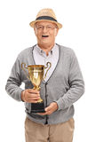 Delighted senior holding a golden trophy. Vertical shot of a delighted senior holding a golden trophy and looking at the camera isolated on white background stock image