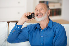 Delighted senior man chatting on a mobile phone. While relaxing on a sofa in his living room, natural close up portrait royalty free stock photography