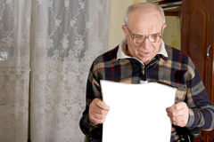 Delighted senior man reading the newspaper Royalty Free Stock Photo
