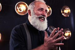 Delighted senior man singing in a retro silver studio microphone. Close-up of emotional man in white shirt and suspenders holding a retro silver studio royalty free stock photos