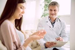 Delighted skillful doctor observing her patient. Professional therapist. Delighted nice skillful doctor smiling and observing his pregnant patient while taking stock photography