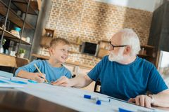Delighted smart boy helping with a blueprint. Young architect. Delighted nice smart boy looking at his grandfather and smiling while helping him with a blueprint Stock Photos