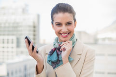 Delighted smart brown haired businesswoman holding a mobile phone Royalty Free Stock Photography
