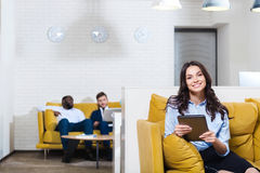 Delighted smiling businesswoman sitting on the couch. Working atmsphere. Joyful delighted beautiful women sitting on the sofa and smiling while her colleagues stock photography