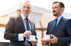 Delighted smiling colleagues drinking coffee royalty free stock images