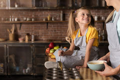 Delighted smiling girl helping her mother preparing the pastry. We enjoy baking together. Delighted amused smiling girl putting the pastry in baking rings while Royalty Free Stock Photography