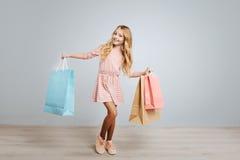 Delighted smiling girl holding shoppign bags Stock Image