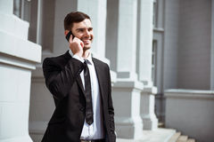Delighted smiling man talking on cell phone. Glad to hear you. Cheerful delighted handsome man smiling and talking on cell phone while expressing gladness royalty free stock photos