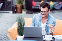 Delighted smiling man using laptop Stock Images