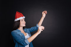 Delighted smiling woman decorating Christmas tree Stock Photo