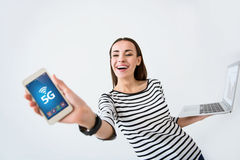 Delighted smiling woman holding cell phone. Express yourself. Overjoyed beautiful smiling woman holding laptop and cell phone while expressing gladness on white stock photo