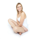 Delighted smiling woman sitting on a bed Stock Photos