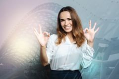 Delighted successful businesswoman feeling happy. Successful career. Delighted positive successful businesswoman smiling and feeling happy while showing OK Royalty Free Stock Image