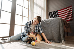 Delighted teenager sitting near his best canine friend Royalty Free Stock Photo