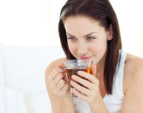 Delighted woman drinking a tea. On her bed Stock Images