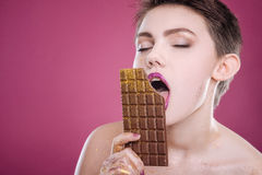 Delighted woman eating chocolate bar Royalty Free Stock Image