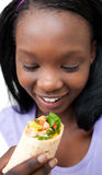 Delighted woman eating a wrap Royalty Free Stock Photo