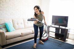 Delighted woman enjoying music and singing with headphones and v. Ecstatic young housewife singing with vacuum cleaner and headphones in living room Stock Image