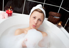 Delighted woman having fun in a bubble bath Stock Images