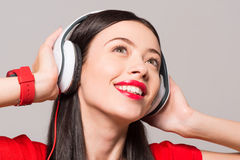 Delighted woman listening to music. Emotionally charged. Portrait of cheerful delighted smiling woman expressing gladness and listening to music royalty free stock image