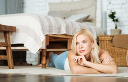 Delighted woman lying on the floor in her bedroom Stock Image
