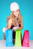 Delighted woman peeking into her shopping bags Stock Photography