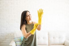 Delighted woman putting on yellow gloves. Young joyous woman putting rubber gloves and getting ready for cleaning Royalty Free Stock Image