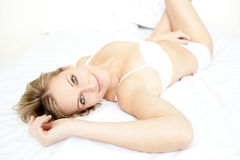 Delighted woman relaxing lying on her bed Royalty Free Stock Images