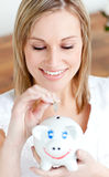 Delighted woman saving money in a piggy-bank. At home Stock Image