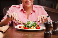 Delighted woman show tongue and going to eat salad with arugula stock image
