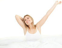 Delighted woman stretching sitting on her bed Stock Photos
