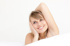 Delighted woman stretching sitting on her bed Stock Photo