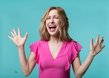 Delighted woman on surprise party. Portrait of thrilled blonde lady standing with raised hands and screaming. Isolated on blue background Royalty Free Stock Photography