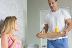 Delighted woman surprised by partner bringing breakfast in bed. Delighted women surprised by partner bringing breakfast in bed at home in bedroom Royalty Free Stock Images