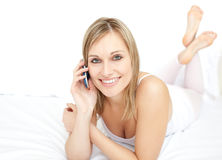 Delighted woman talking on phone lying on her bed Stock Photography