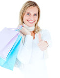 Delighted woman with thumb up and shopping bags Royalty Free Stock Image