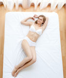 Delighted woman in underwear lying Stock Photo