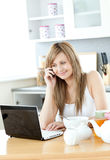 Delighted woman using a laptop in the kitchen. At home Stock Images
