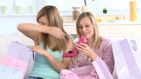 Delighted women showing their new shoes. Sitting between shopping bags on the couch stock video footage