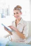 Delighted young blonde businesswoman pointing her tablet pc Stock Photos