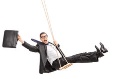 Delighted young businessman swinging on a swing. Studio shot of a delighted young businessman swinging on a swing and holding a suitcase isolated on white stock images