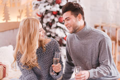Delighted young couple celebrating New Years Eve. Happy New Year. Delighted young nice couple sitting together and drinking champagne while celebrating New Years royalty free stock photos