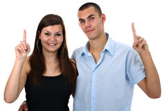 Delighted young couple pointing their fingers up Royalty Free Stock Images