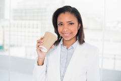 Delighted young dark haired businesswoman holding a cup of coffee Stock Photography