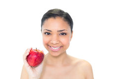 Delighted young dark haired model holding a red apple Royalty Free Stock Images