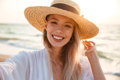 Delighted young girl in summer hat and swimwear. Spending time at the beach, taking a selfie Royalty Free Stock Photo