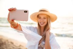 Delighted young girl in summer hat and swimwear. Spending time at the beach, taking a selfie with outsretched hand Stock Image