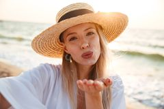 Delighted young girl in summer hat and swimwear. Spending time at the beach, taking a selfie, sending kiss Stock Photo