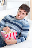 Delighted young man eating popcorn lying on a sofa Stock Image